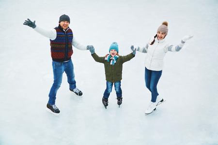 mama e hijo: Familia feliz de patinadores mirando a la cámara en la pista de patinaje