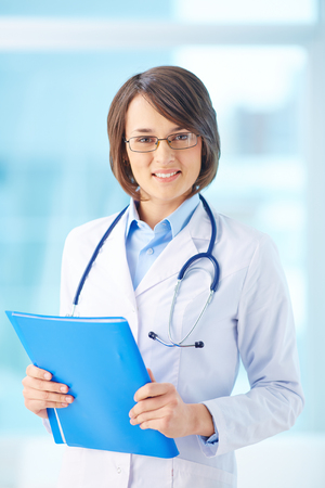 clinician: Young clinician with document looking at camera Stock Photo