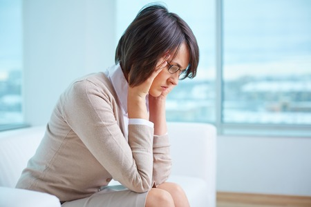 distraught: Young distraught woman sitting on sofa Stock Photo