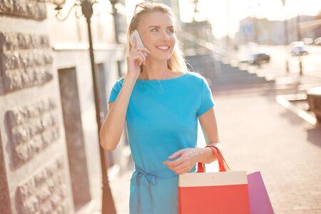 llamando: Mujer joven con bolsas de compras llamando al aire libre