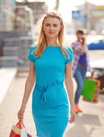 Junge Kunden mit Einkaufstüten auf der Suche Kamera im Freien Standard-Bild - 49880816
