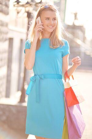 llamando: Comprador joven con bolsas llamando al aire libre