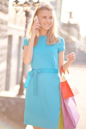 shopper: Young shopper with bags calling outdoors