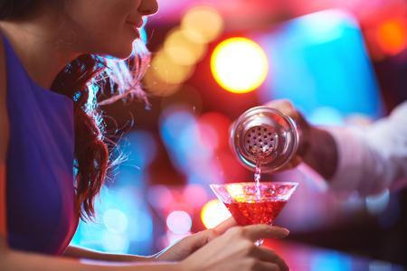 barman: Girl holding martini glass while barman pouring cocktail