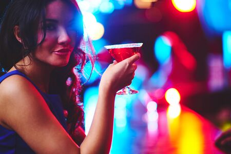drinks on bar: Girl with cocktail looking at camera in the bar