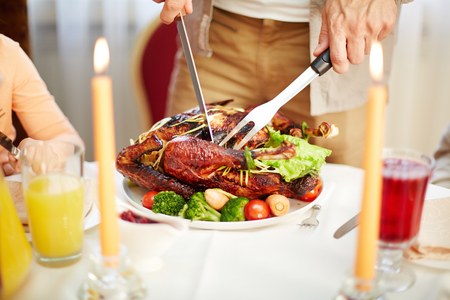 occasion: Man cutting roasted turkey between burning candles