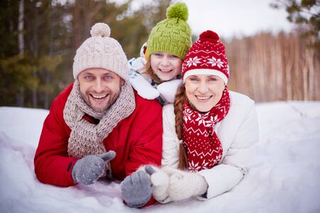 snowdrift: Happy family lying in snowdrift in winter forest