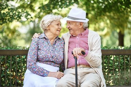 happy seniors: Happy seniors sitting on bench in the park and enjoying summer day Stock Photo