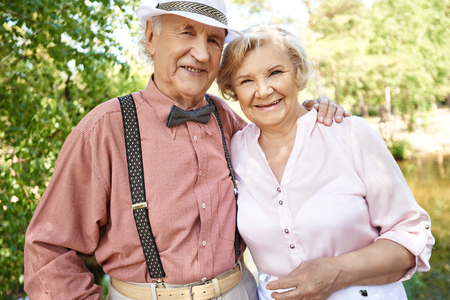natural looking: Elderly couple in smart casual-wear looking at camera in natural environment in summer Stock Photo