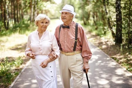persona de la tercera edad: Pareja de ancianos en smart casual-desgaste caminar en el parque de verano