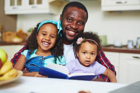 reading book: Happy African-American family of three reading book