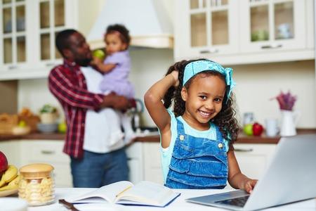 familias jovenes: Feliz niña afroamericana mirando a la cámara, mientras que la creación de redes en la cocina Foto de archivo
