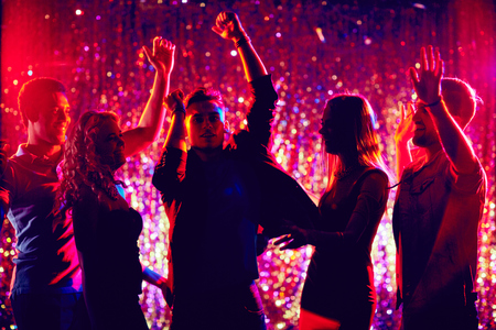adult entertainment: Group of friendly young people dancing in the night club Stock Photo