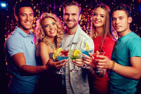 festive occasions: Group of cheerful friends toasting with cocktails at party
