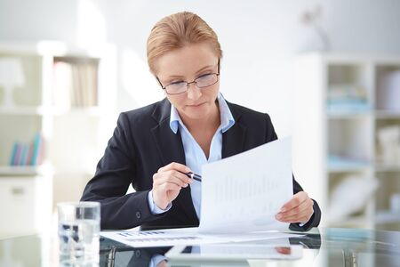 executive woman: Young businesswoman working with documents Stock Photo