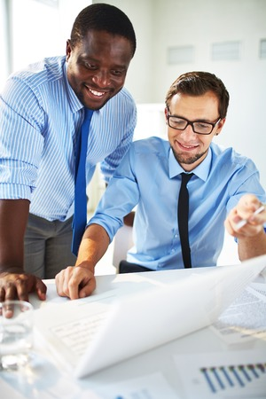 people working together: Two handsome businessmen working together on a project sitting at a table in the office