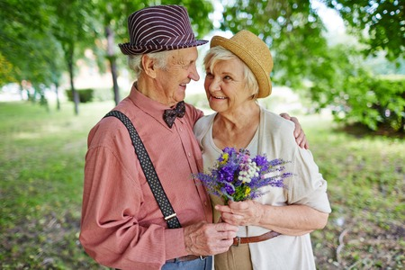 romantic couples: Mature lovely couple with flowers outdoors Stock Photo