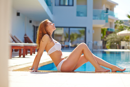 poolside: Young woman relaxing and tanning at resort poolside
