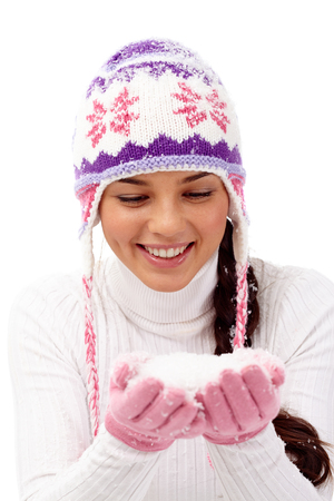 Smiling girl holding snow in her hands photo