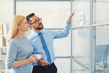 business office: Businessman showing financial graphs to his colleague