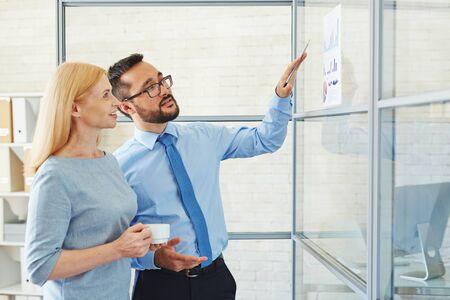 personas de pie: De negocios que muestra gráficos financieros a su colega Foto de archivo