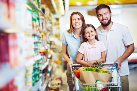grocery shopper: Family with chopping cart during shopping at vegetable supermarket