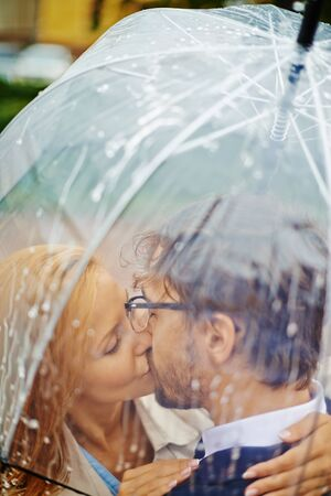 adult couple: Young couple kissing under the umbrella
