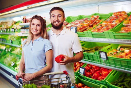 happy shopper: Young family couple choosing vegetables in supermarket