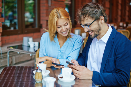 couple outdoor: Smiling young couple using smartphones at cafe