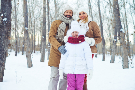 guy portrait: Family of three standing together in winter forest