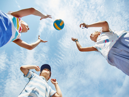the view from below: View from below of kids playing ball Stock Photo