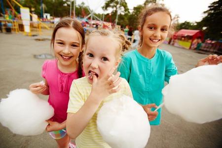 cotton candy: Ni�as felices comiendo algod�n de az�car en el parque