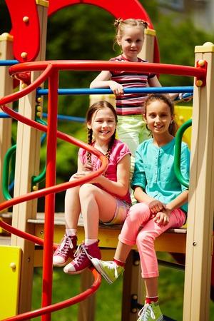 niños sentados: Niños sonrientes que se divierten al aire libre