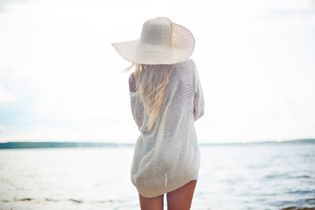 Young woman standing on the beach and enjoying beautiful view