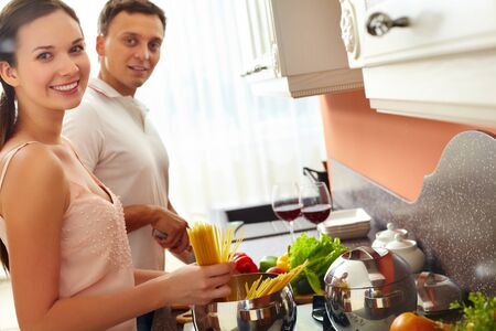 Young woman cooking spaghetti while her husband cutting vegetables photo