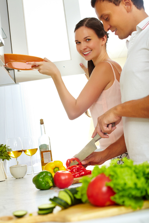 Happy housewife looking at camera while her husband cutting vegetables in the kitchen photo