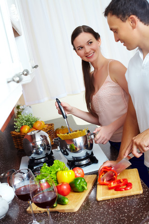 Young couple cooking spaghetti and salad in the kitchen photo