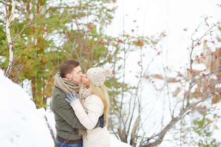 young couple kiss: Young couple kissing in winter park Stock Photo