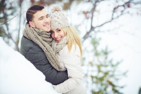 Happy young man embracing his girlfriend outdoors Stock Photo