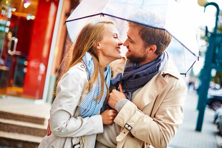 amorous: Amorous young couple laughing under umbrella