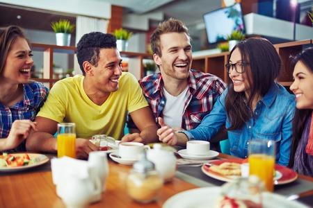 almuerzo: Adolescentes felices que hablan durante el almuerzo en la cafetería