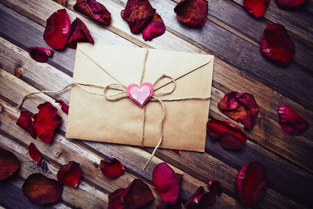 sealed: Sealed envelope decorated with small pink heart among rose petals Stock Photo