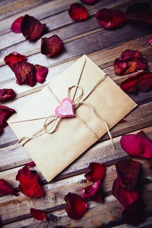 sealed: Sealed envelope with decorative heart among dry rose petals Stock Photo