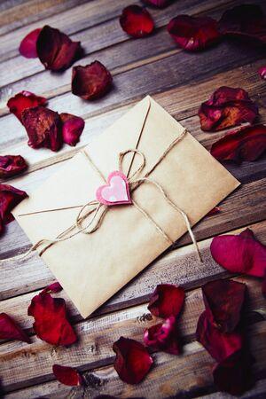 envelope decoration: Sealed envelope with decorative heart among dry rose petals Stock Photo