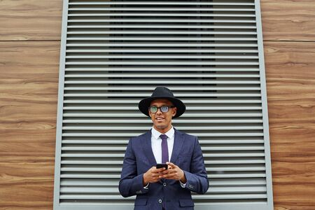 jalousie: Elegant businessman with cellphone standing against jalousie Stock Photo