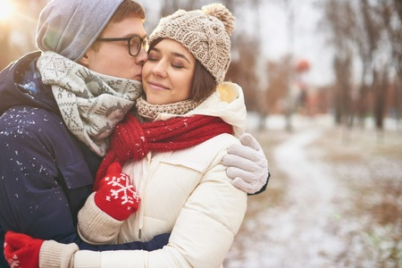 amorous woman: Happy guy kissing his girlfriend outdoors
