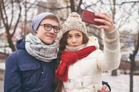 amorous: Amorous dates in winter-wear making selfie