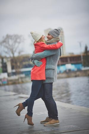 pareja abrazada: Pareja amorosa feliz abrazando en entorno urbano Foto de archivo