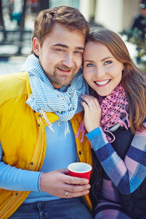 amorous: Amorous couple in casual-wear looking at camera outdoors Stock Photo