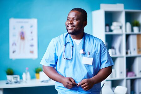 clinician: Smiling clinician in hospital looking aside Stock Photo